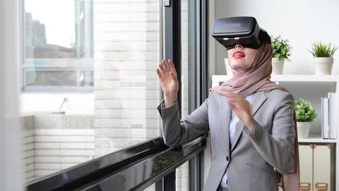 happy pretty muslim business woman using virtual reality goggles watching company case plan and touching simulation screen to move document.