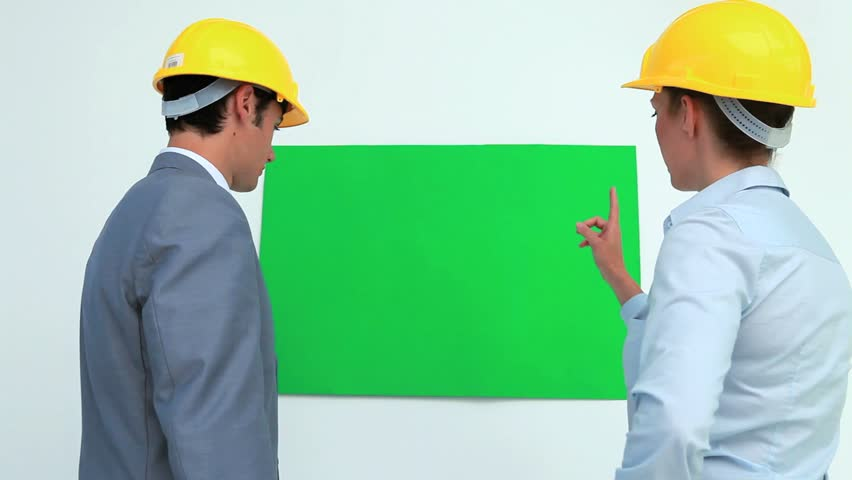 Architects talking in front of a blank space on the wall while wearing safety helmet | Shutterstock HD Video #3042043