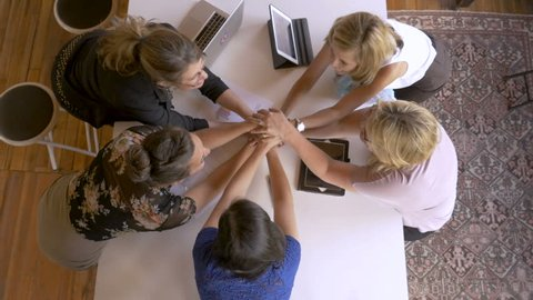 Diverse young millennial female entrepreneurs celebrating successful teamwork with smart phone digital tablet and laptop technology in business cheering and fist bumping overhead shot in slow motion