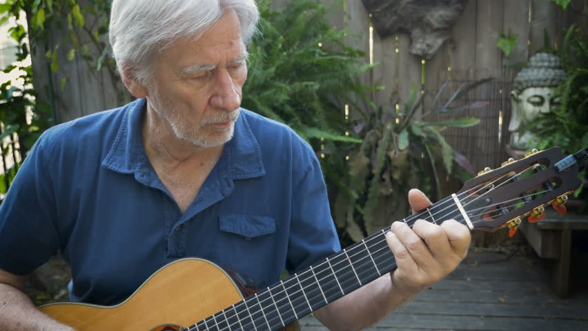 Handsome healthy retired baby boomer senior adult man playing acoustic guitar outside in his garden dolly shot