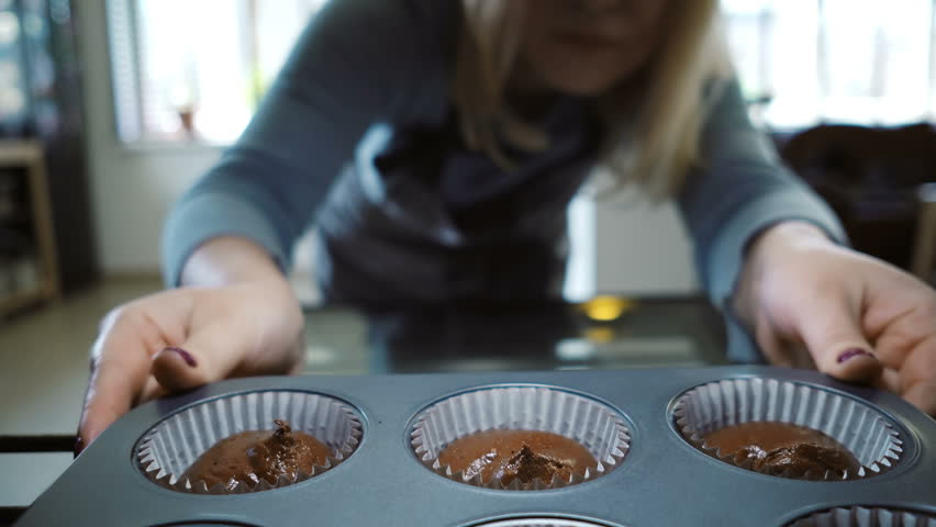 View inside: young woman open oven and putting in baking tray for cupcakes. Female dancing while waiting the desserts.