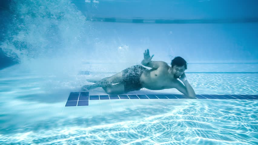 Young man lay down on bottom of pool. Smiling and waving his hand under water. Slow motion. Underwater photography. | Shutterstock HD Video #30453973
