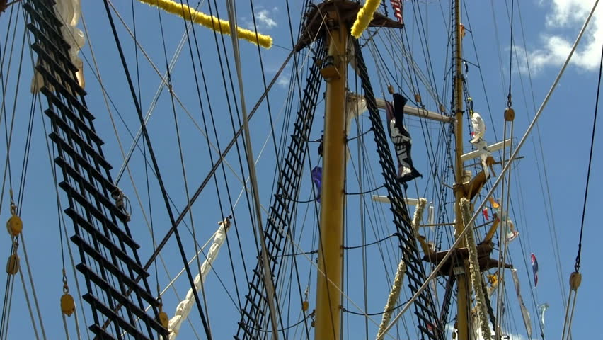 Masts, rigging, banners and pirate flag waving in wind on Indonesian tall ship Dewaruci against blue sky