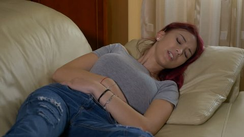 Redhead teenager girl with acute pms ovary menstrual cramp pain laying on couch with her hands on abdomen