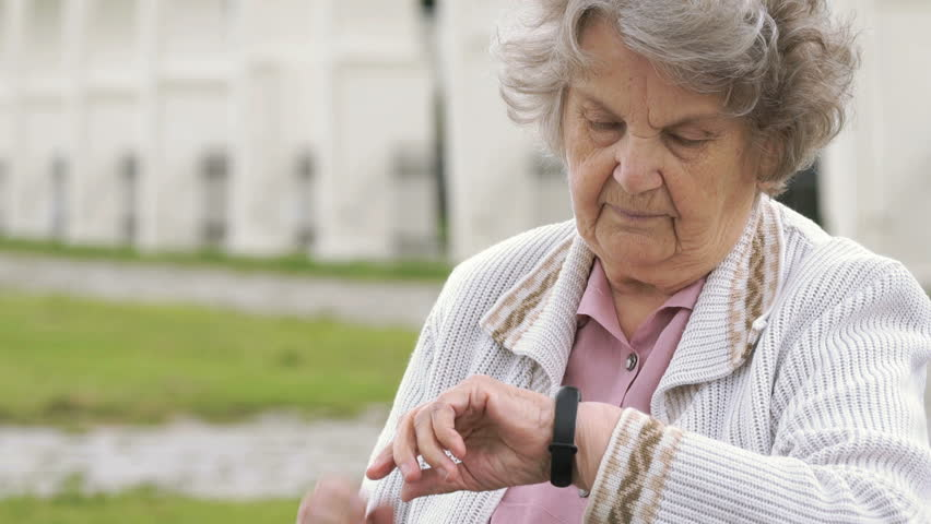 Black wristband. Mature old woman with gray hair aged 80s dressed in white jacket looks at the results of physical activity using a wristband fitness tracker outdoors in summer