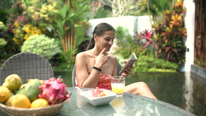 Attractive woman laughing while watching something funny on smartphone, steadycam shot