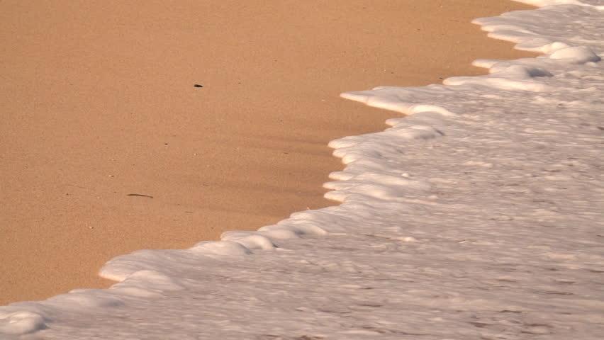SLOW MOTION, CLOSE UP: Foamy ocean waves washing red sandy beach on tropical paradise island Bali. Swash wave traveling up the gorgeous sea shore with orange sand. Bubbly ripple swashing scenic coast