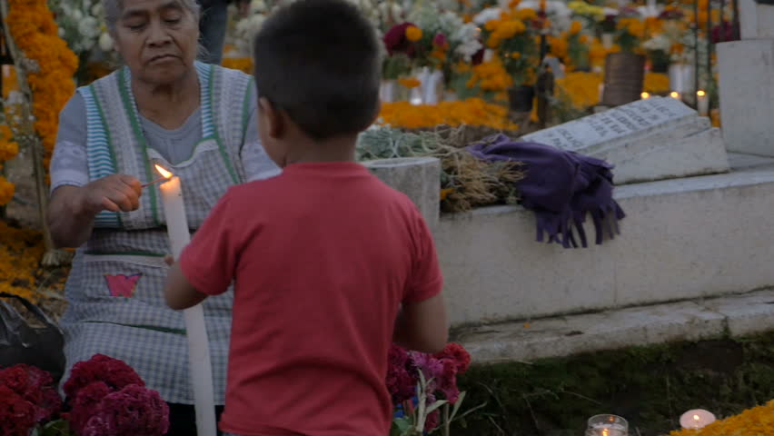 TZURUMUTARO, MEXICO - NOVEMBER 1, 2016 - Young Mexican boy helping his grandmother light a candle at the alter of the grave of his ancestors during Day of the Dead