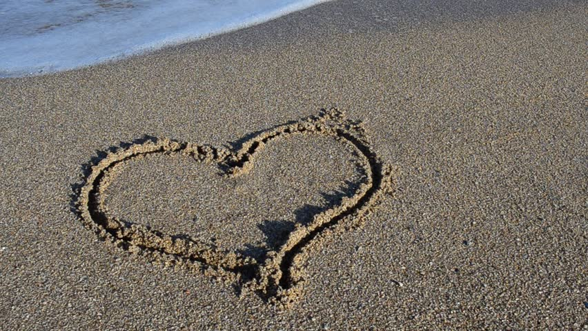 The drawing heart on sand. Heart is washed away by a sea wave.Shooting on the beach.