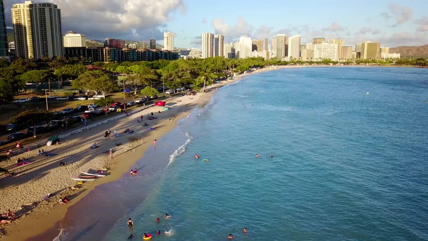 Aerial of Ala Moana Beach Park near Magic Island Lagoon in Waikiki. Blue ocean water with condos and hotel buildings nearby. Calm gentle water lapping on white sand beach.  Tourist vacation paradise.