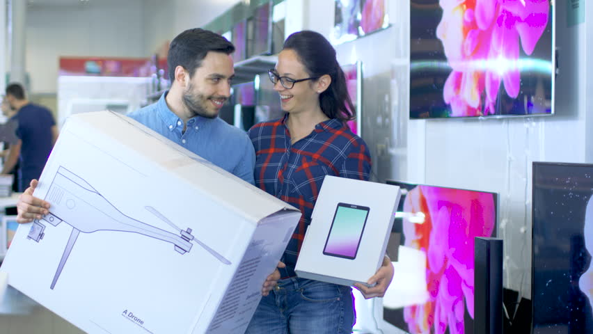 In the Electronics Store Happy Young Couple Poses with Newly Purchased Drone and Tablet Computer. Store is Big and Bright, Has All the Latest TV's, Cameras and Smartphones.Shot on RED EPIC-W 8K Camera | Shutterstock HD Video #30542293