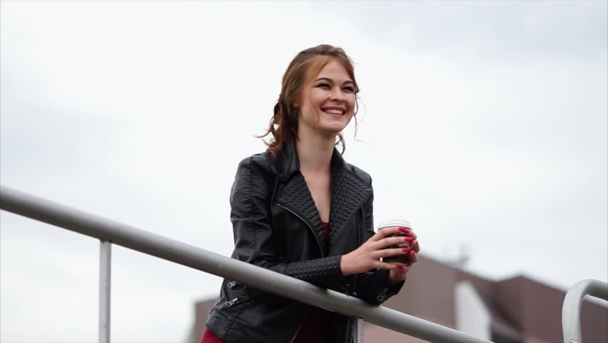 Cheerful young woman with coffee outdoor. She leaning on metal rails and looking at the city