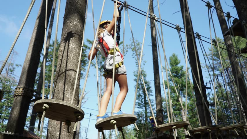 A little girl in a rope adventure park climbing and overcoming obstacles  | Shutterstock HD Video #30570823