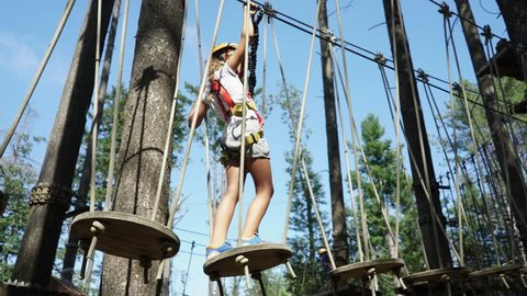 A little girl in a rope adventure park climbing and overcoming obstacles