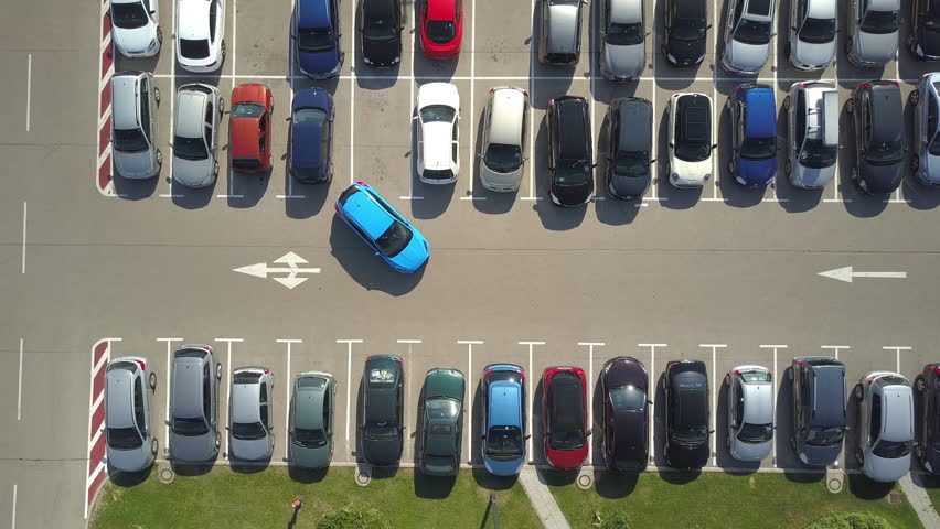AERIAL TOP DOWN: Flying above female bad driver incapable to park a car on parking space in crowded parking lot. Driver having problems, unable to park a car in parking spot. Parking fail on parkspace