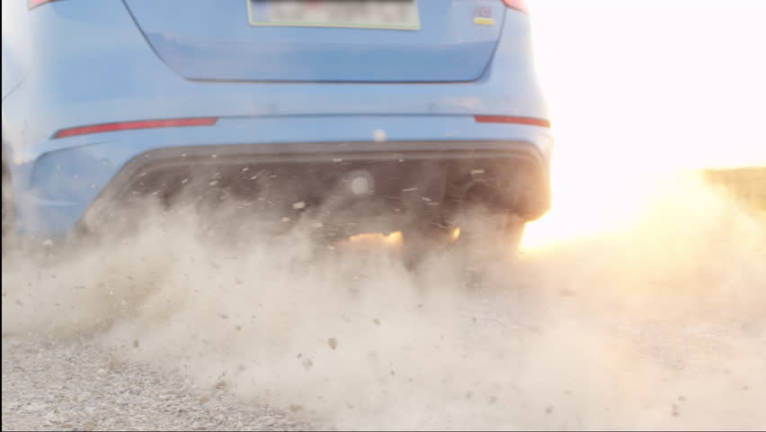SLOW MOTION CLOSE UP: Sports car starts & quickly drives away from a dusty macadam dirt road raising sand, rocks and stones at dusk. Sportive auto performing burnout at beautiful golden summer sunset