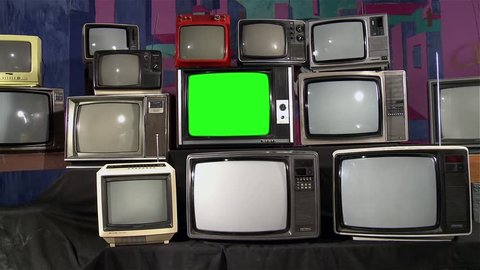 "Television with Green Screen in the Middle of Many Tvs. Aesthetics of the 80s. Ready to Replace Green Screen with Any Footage or Picture you Want. You Can Do it With ""Keying"" (Chroma Key) Effect."