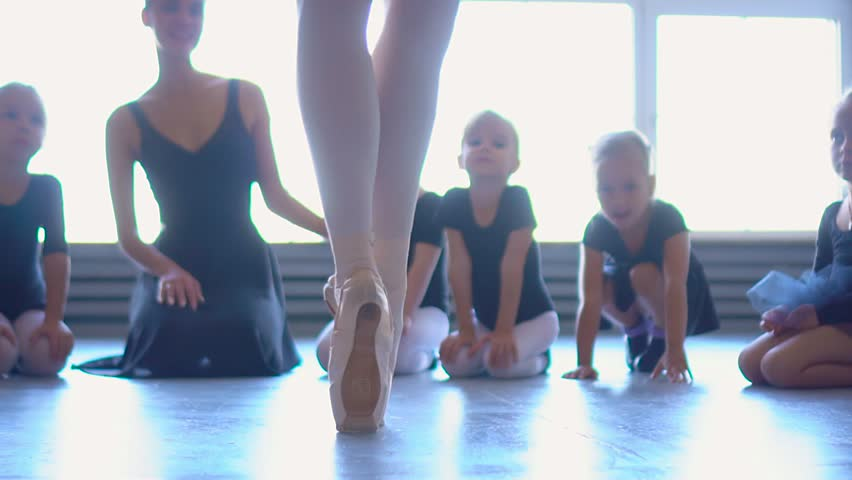 Girl dancer in ballet school learns to dance. Little Ballerina in training in black dancing suit. Children's ballet school. Young ballerinas jumping in training. School of ballet. Feet closeup