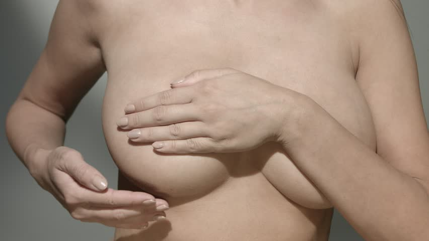 Topless woman examining her breast for cancer signs - slow motion
