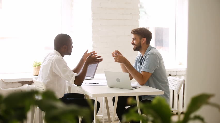 African american and caucasian businessmen talking in loft office, diverse colleagues joking laughing in friendly easygoing coworking atmosphere, good relations at workplace, making friends at work | Shutterstock HD Video #30602863