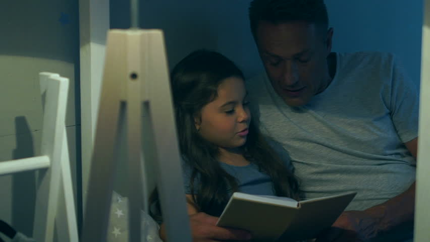 Positive caring father reading a book with his cute daughter   Shutterstock HD Video #30605953