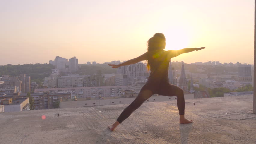 Yoga exercises on the rooftop at sunset. Young sporty woman doing yoga and meditation on the roof.