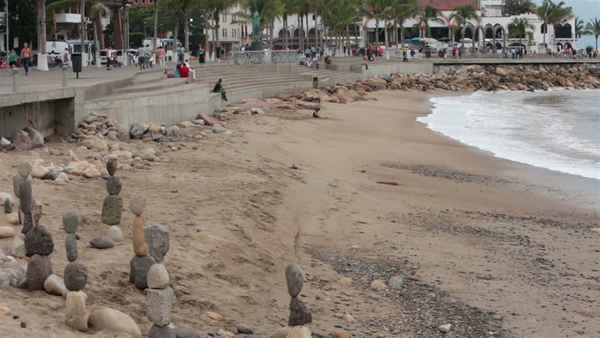 PUERTO VALLARTA, MEXICO NOV 2012: Tourism attraction and income for locals. Malecon Boardwalk beach rocks. Tourist area shore of Banderas Bay, Pacific Ocean. Work for tips and recognition.