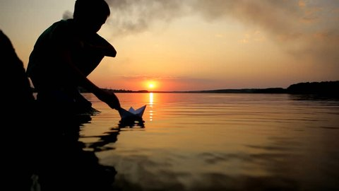 Little boy playing with paper boat on water