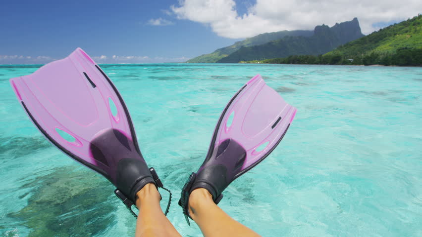 Travel vacation beach concept Snorkel feet snorkeler having fun with pink snorkel fins. Legs closeup of swimmer relaxing on sea background, Happy vacation travel to tropical vacations.