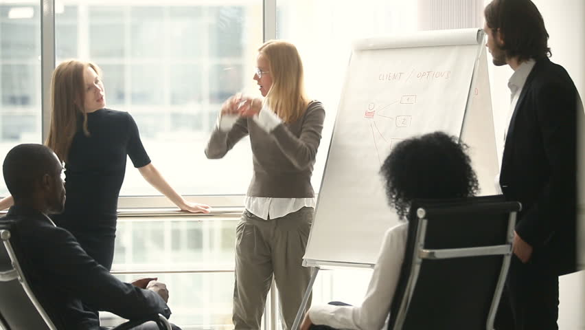 Female manager presents new project plan to colleagues at meeting, explaining ideas on flipchart to coworkers in office, businesswoman gives presentation, discussing ideas with diverse business team | Shutterstock HD Video #30610963