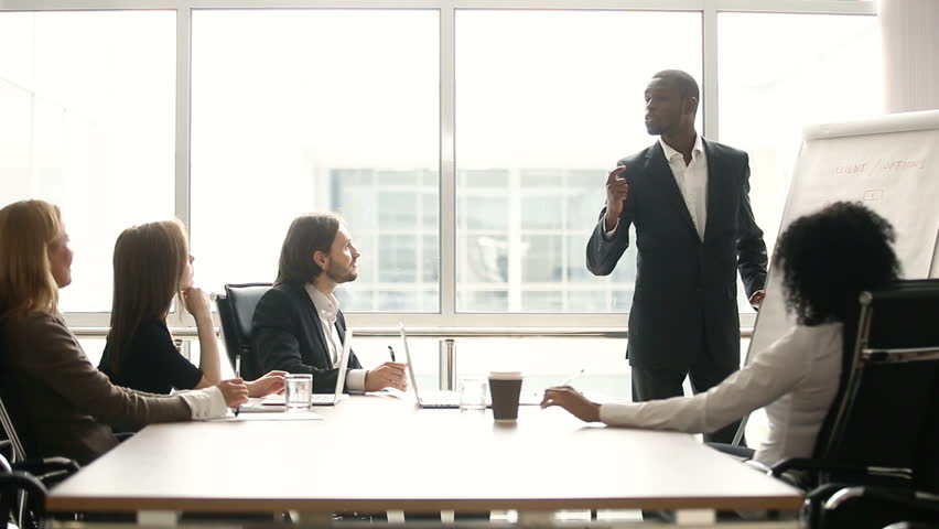 African american coach gives corporate presentation for businesspeople in office, dark skinned businessman presents new business plan on whiteboard, speaking to clients listening speaker at meeting #30610993
