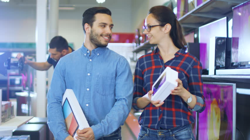 Happy Couple Walking In the Electronics Store, They've Purchased Latest Model of the Tablet Computer for Him and New Smartphone for Her. Shopping Center is Big, Bright and Full of Newest Electronics. | Shutterstock HD Video #30614500