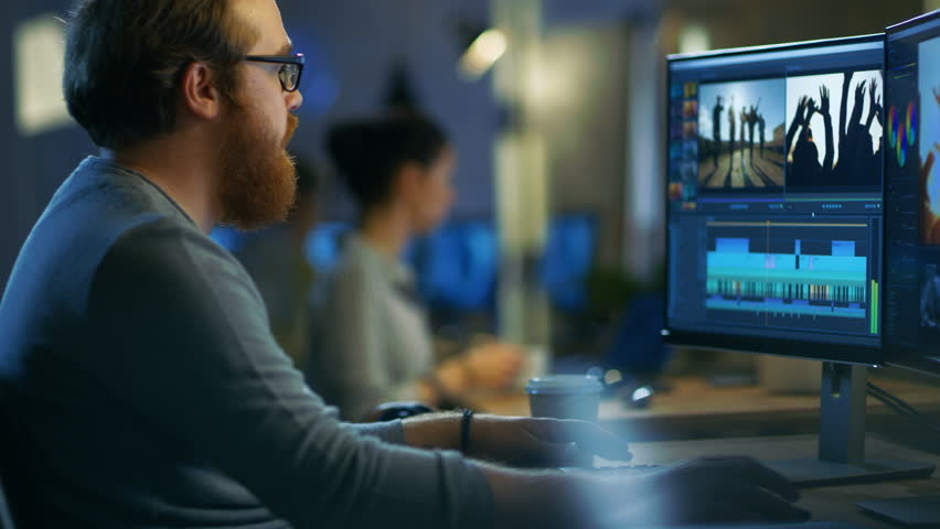 Male Video Editor Works with Footage and Sound on His Personal Computer with Two Displays. He Works in a Cool Office Loft with Other Creative People. Shot on RED EPIC-W 8K Helium Cinema Camera. | Shutterstock HD Video #30614503
