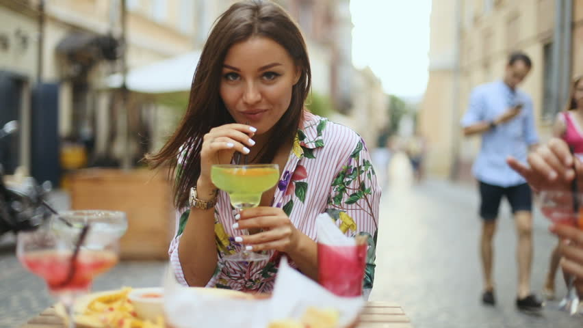 Young pretty sexy girl drinking cold beverage cocktail outdoor in city street cafe, slow motion shot
