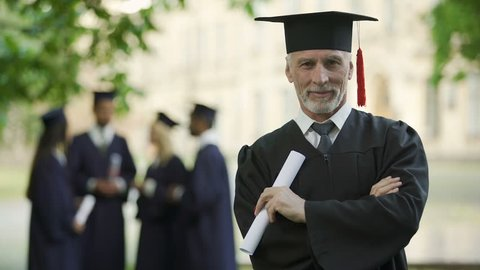 Aged man in graduation outfit, professor obtaining new degree, academic career
