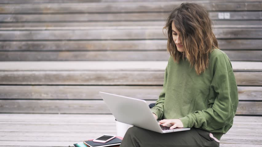 Side view of a beautiful young woman wearing a green sweatshirt sitting on the stairs outside and typing at her laptop keyboard. Locked down real time establishing shot