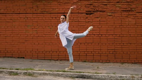 Modern ballet dancer. The young sporty woman dancing against the red brick wall in the street. 4K