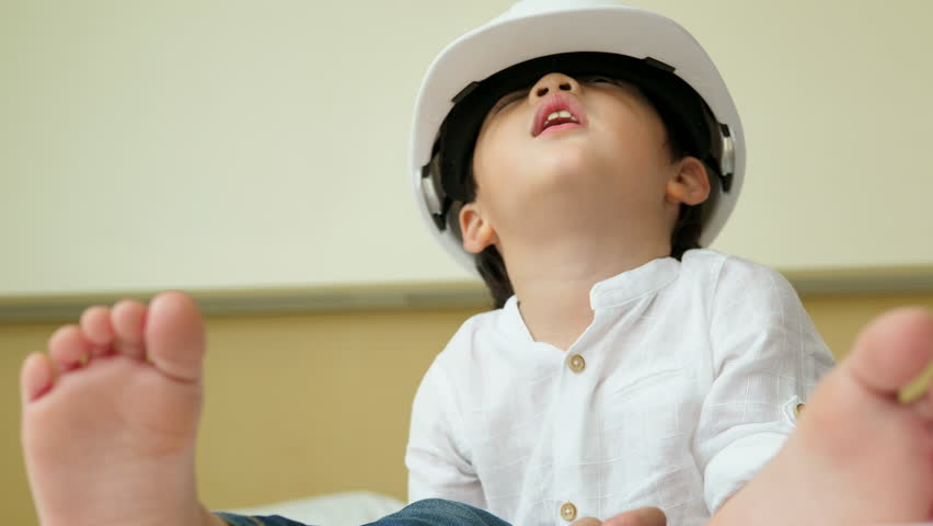 Advertising, Kids and education concept - A child architect. Asian boy in white safety helmet at home and focus dreaming about future profession.  | Shutterstock HD Video #30656953