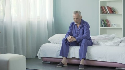 Annoyed old man sitting on bed after awakening, having bad mood in morning