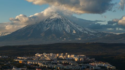 Kamchatka time lapse: top view of Petropavlovsk-Kamchatsky City on background beautiful clouds drifting across sky and cone of Koryak Volcano (Koryaksky Volcano). Kamchatka Peninsula, Russian Far East