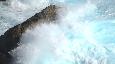SLOW MOTION CLOSE UP: Huge turbulent foamy ocean wave breaking. Perfect barrel wave rolling upon the shore splashing. Big powerful swell wave crushing over the sharp rocky reef spraying sea waterdrops