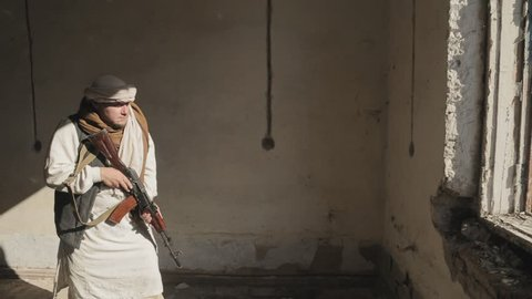 Two armed mujahideen shoot the rifle at the window on the enemy