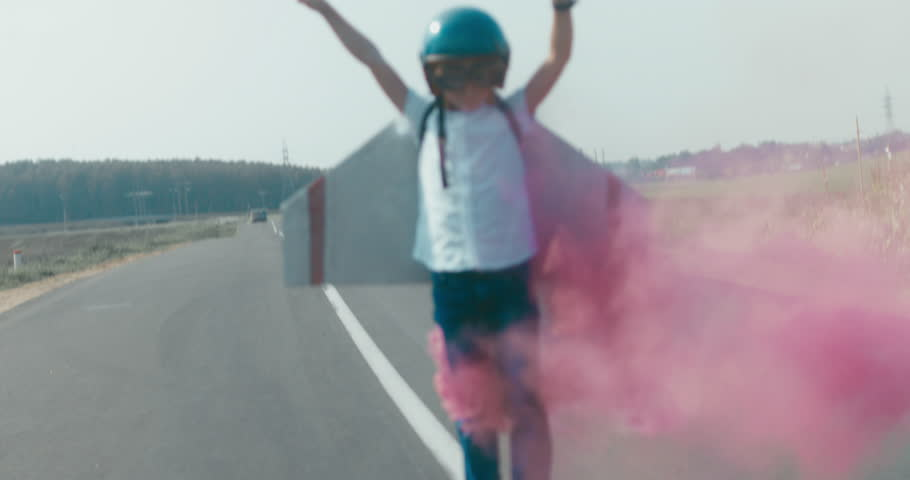 Little boy wearing helmet and styrofoam wings standing on a rural road, pretending to be a pilot. 4K UHD RAW edited footage | Shutterstock HD Video #30705523