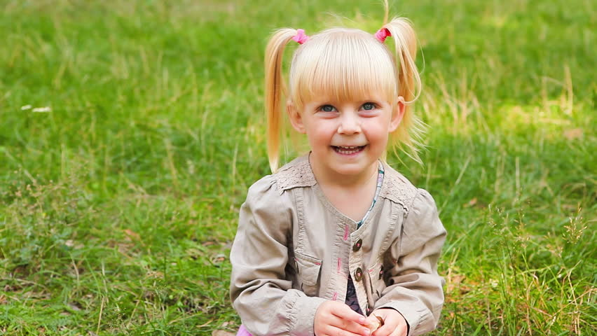 Cute little girl show thumbs up and smile outdoors in summer