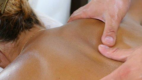 Deep tissue massage closeup view. Masseur doing massage on woman body in the spa salon. Beauty treatment concept, slow motion