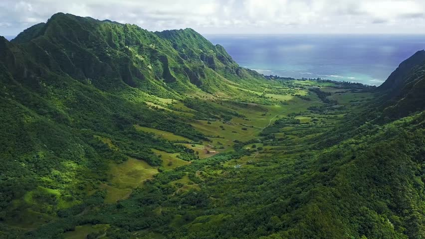 Aerial View of KoOlau Mountain Range near Kaneohe Oahu Hawaii Island. Lush beautiful green valley and cliffs.  Blue Sky, tropical ocean, where Jurassic Park was filmed.  4K UHD drone footage. Movie.