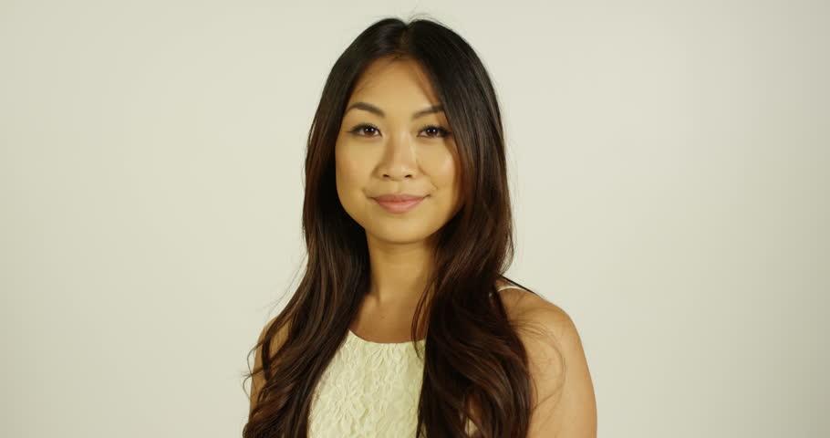 4K Headshot of smiling Asian model posing on white background in studio photoshoot. Slow motion.
