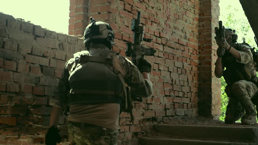 Airsoft men with guns going up stairs. Training to fight in urban territory.