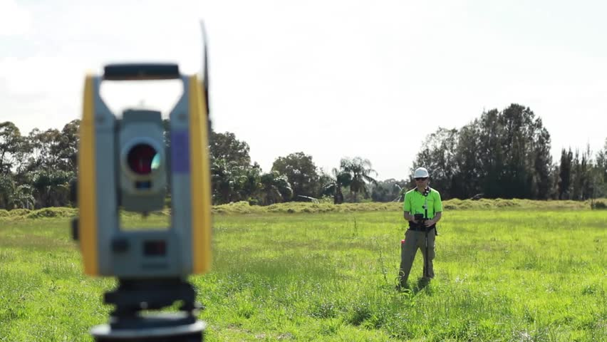 Land Surveyor Takes Measurements In A Field Using A Robotic Theodolite