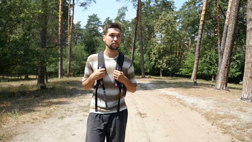 A relaxed young man with a backpack goes along a footpath in a pine forest on a sunny day in summer in slow motion. The forest looks natural and nice. #30785893